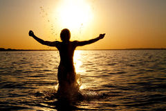 Splash out. Swimmer jumping out of sea water on golden sunrise Stock Photography