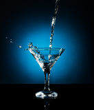 Splash from pouring martini into the glass. Object on a blue background Royalty Free Stock Photos