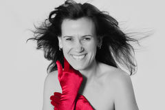 A splash of red. A beautiful and happy woman wearing only red gloves and smiling Stock Photo