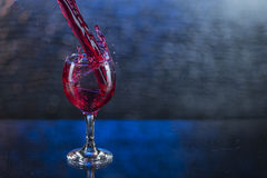 Splash in red juice or wine in a wineglass.  Royalty Free Stock Photos