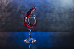 Splash in red juice or wine in a wineglass.  Royalty Free Stock Photography