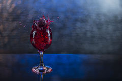 Splash in red juice or wine in a wineglass.  Royalty Free Stock Images