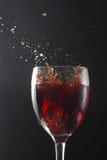 Splash Red Wine. Grape splashing in Red wine Glass Royalty Free Stock Image
