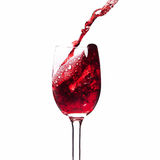 Splash red wine in a glass. Stock Images
