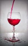 Splash of red wine in glass stock image