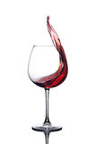 Splash of red wine in a glass on a white background. Splash of red wine in a glass on a white background with reflection Royalty Free Stock Photos