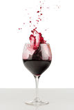 Splash of red wine in a wineglass. Stock Photos