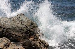 Splash on rocks. A wave crashes into a rock Stock Photo