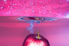 Splash-serie: red apple with red background Stock Photos
