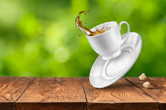 Splash of tea on wooden table against green background Stock Photography