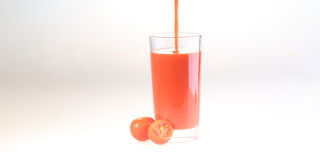 Splash in tomato juice in a transparent glass on a white backgro. Und, dynamics of a liquid stock image