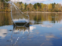 Splash on a unruffled surface of water Royalty Free Stock Image