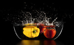 Splash vegetables. Image is posed on dark background Stock Photos