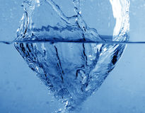 Splash water. Photo of seething fresh water on the blue background Stock Image