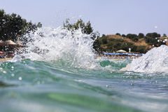 Splash water of Aegean Sea on the background of beach. Royalty Free Stock Photography