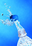 A splash of water from a bottle. Stock Photography