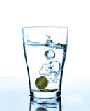 Splash of water and coins in a glass. Water splashes when a coin dropped in to a glass royalty free stock photos