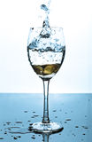 Splash of water and coins in a glass. Water splashes when a coin dropped in to a glass royalty free stock photography