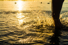A splash of water created by the boy`s foot, the orange trace of the scorching sun Royalty Free Stock Photography