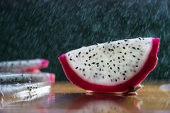 A splash of water drips into the pitaya. On a table stock images