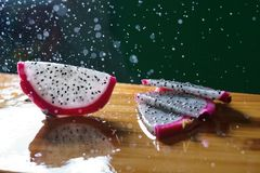 A splash of water drips into the pitaya. On a table royalty free stock photography