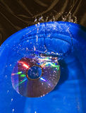 Splash in water at falling CD disk Stock Photos