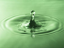 Splash of water from falling drop green filter Royalty Free Stock Photo