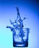 Splash of water in a glass Stock Images