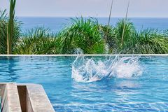 Splash water in the pool from a ducked person. Outdoor pool on background  palm and sea. Back view. Splash water in the pool from a ducked person. Outdoor pool Royalty Free Stock Photo