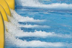 Splash of water from slide in swimming pool Royalty Free Stock Photos