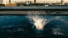 splash of water after someone jumped to the water at sunset at a rooftop pool royalty free stock photography