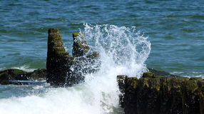Splash. Water splashes over rocks at the shore Royalty Free Stock Images