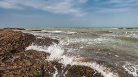 Splash of waves on a rocky seashore. Landscape stock image