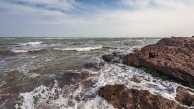 Splash of waves on a rocky seashore. Landscape stock images