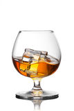 Splash of whiskey with ice in glass. Isolated on white background Royalty Free Stock Photography