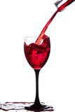 Splash of wine in the cup filling Royalty Free Stock Photography