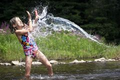 Splash! A young girl gets soaked by water. A young child getting splashed by a stream of water in knee deep water at a river, she is holding a snorkel Stock Images