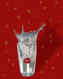 Splashes 2 on red. Stawberry dropped in glass with water with splashes isolated with clipping path Stock Photography