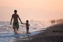 In the splashes. Father and his son have vacations on the sea Stock Image