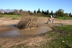 Splashes. Young biker riding through a puddle of muddy water Stock Photos