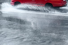 Splashes by car through flood water Stock Photography