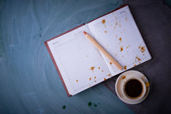 Splashes of coffee on the opened notebook. A cup of coffee, tea cup, a pencil. On dark background. Stock Image