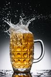 Splashes of cold light alcohol beer. In mug stock images