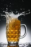 Splashes of cold light beer in mug stock images