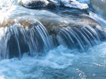 Splashes and drops of water in a small waterfall in winter stock photography
