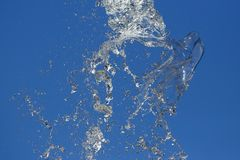 Splashes of flying water from the fountain against the blue sky Stock Photos