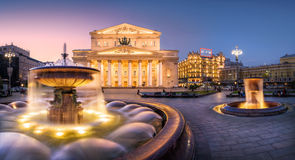 Splashes of a fountain at the Bolshoy Theatre. The jets of a fountain near the Bolshoi Theater with evening lights royalty free stock image