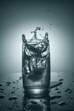 Splashes in a glass of pure cold water Stock Photography