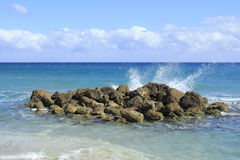 Splashes from the Ocean. On a bright sunny day waves splash onto rocks on Deerfield Beach, Florida a beautiful scene and memorable because of it splendid beauty Stock Photos