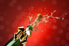 Splashes when opening bottle. Popping cork from Champaign bottle with lot's of splashes red background stock photo